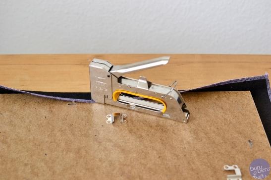 Schritt 3: Stoff mit der Tackerpistole auf der Rückseite des Brettes fixieren.