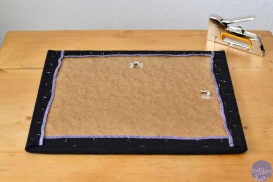 Stoff dabei stramm ziehen und die Ecken schön einschlagen. Falls nötig Stoff bei den Ecken hinten ein wenig stutzen.